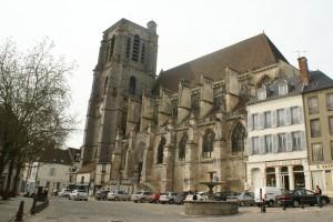 Place de la République. Trois maisons de poupée d'allure médiévale sont accolées à l'église: les échoppes